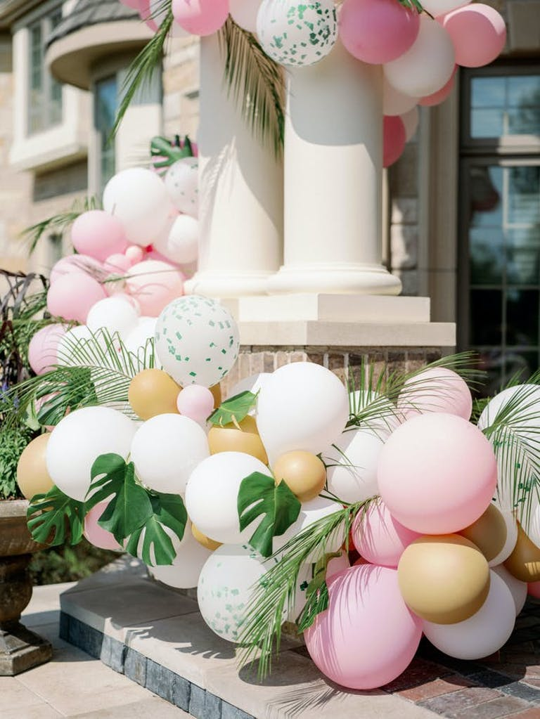 Two columns near the front door of the house surrounded by muted colored balloons in pink, gold, white and silver, and monstera leaves are mixed in