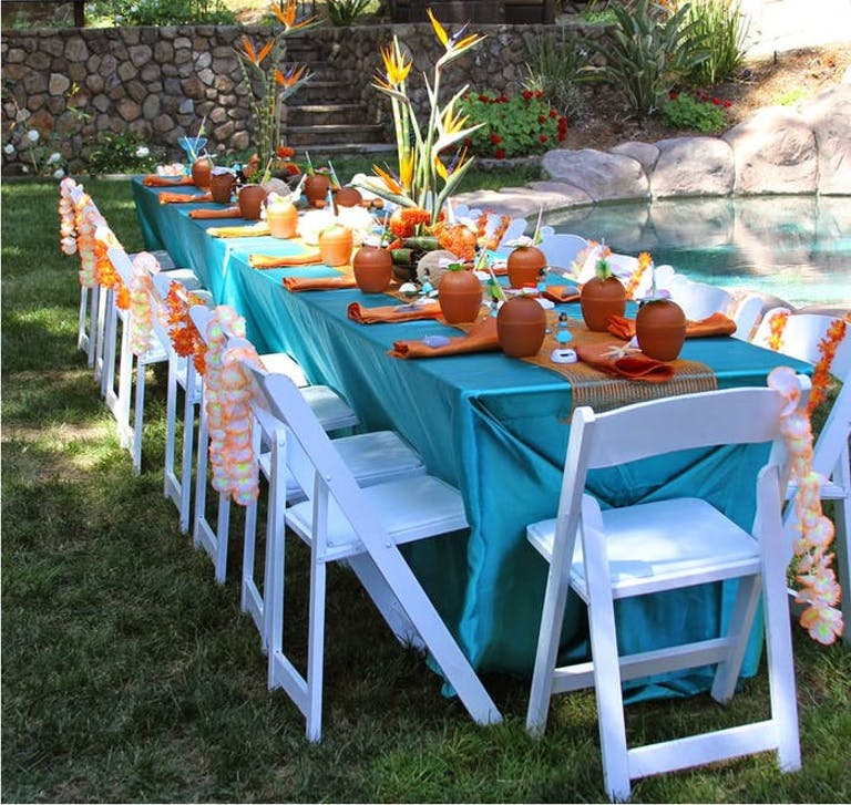A long table with a blue linen with orange and white leis