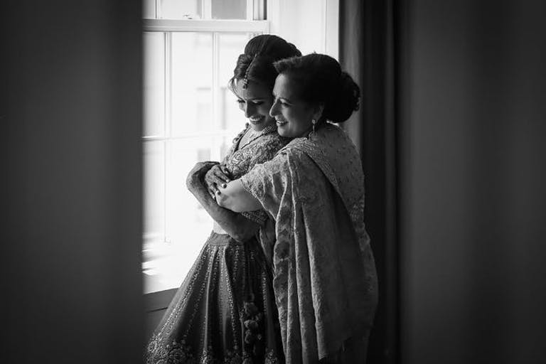 A black and white photo of a mother hugging her daughter from behind in front of a window
