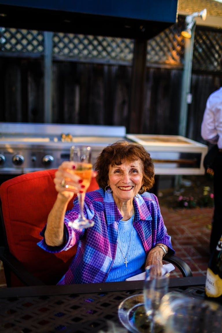 An older woman wearing a blue shirt and purple flannel sits on a red couch and raises a glass of Champagne.