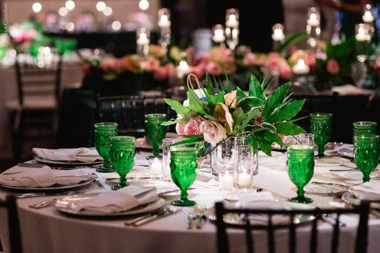 A round table with vintage place settings. Green glass water cups and greenery centerpiece