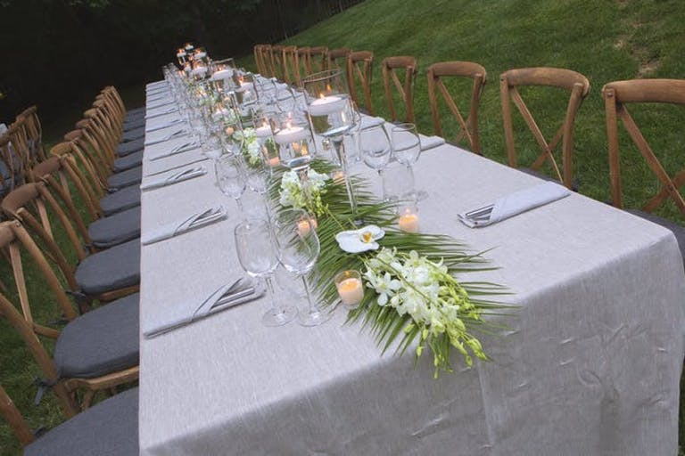 An angled photo of a long table with a white linen and wooden chairs along it. Greenery is down the middle