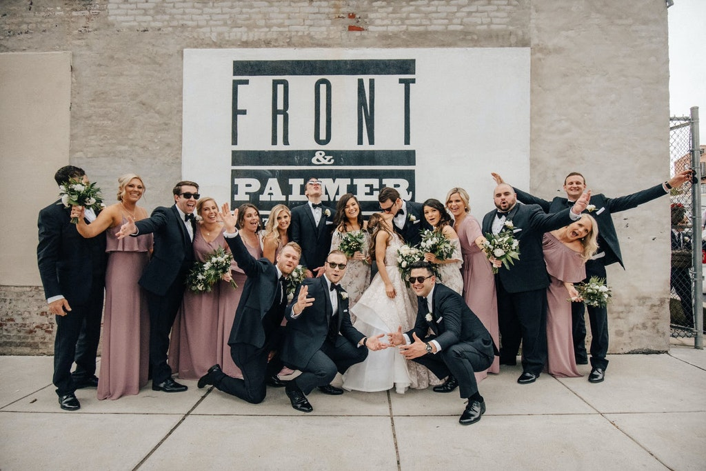 """A bride and groom kiss while surrounded by their groomsmen and bridesmaids. The bridesmaids wear rose-colored dresses and hold green and white bouquets. They are all posing in front a light brick wall with a giant black and white sign that reads """"Front & Palmer."""""""