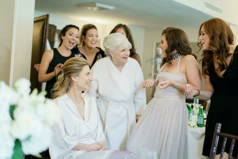 Mother of bride and friends get ready with bride before wedding.