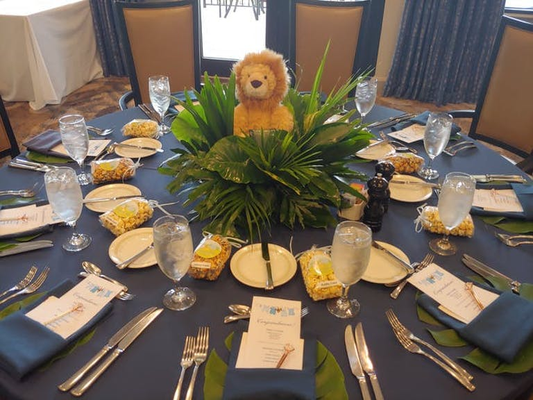 A round table with a navy blue linen and green place settings. A fern in the center with a stuffed lion sitting on it