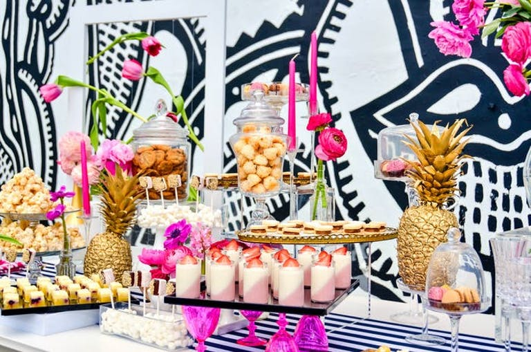 A dessert table against a black and white graffiti wall
