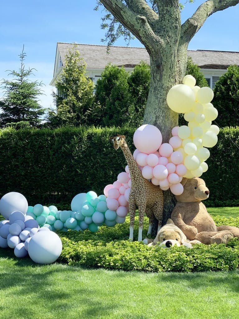 A balloon installation that goes from the ground up a tree and over a toy giraffe