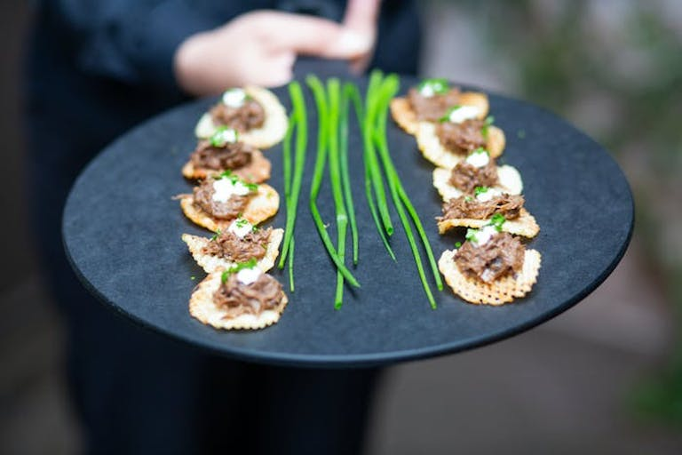 an appetizer on a slate board. Chives are down the middle