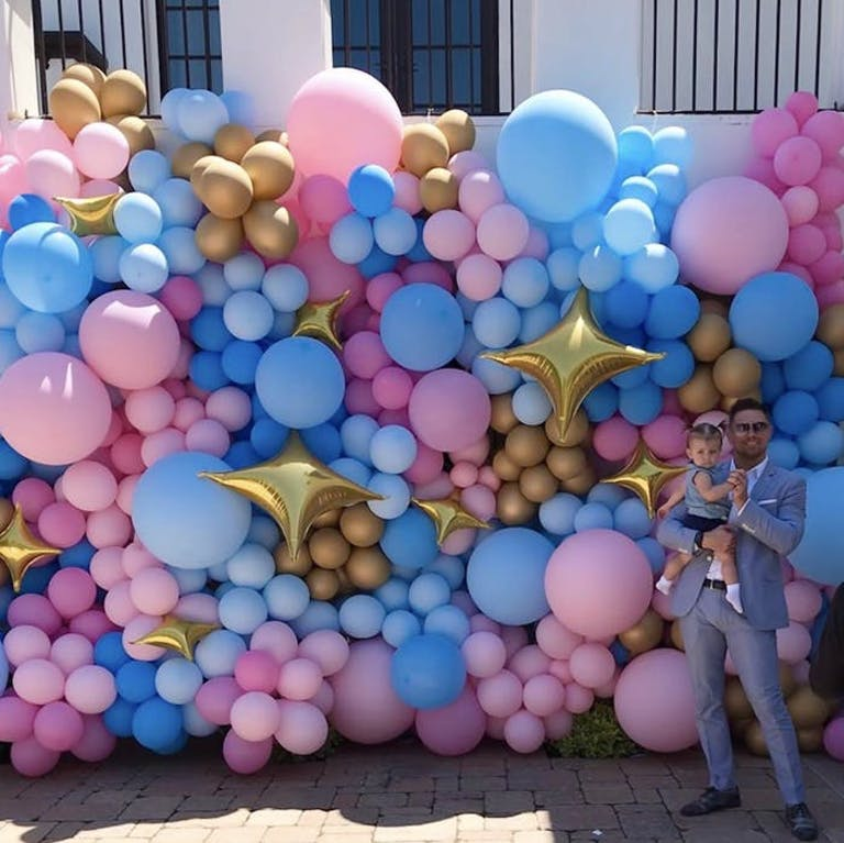 a man in a suit holding a baby in front of a wall of pink and blue balloons outside