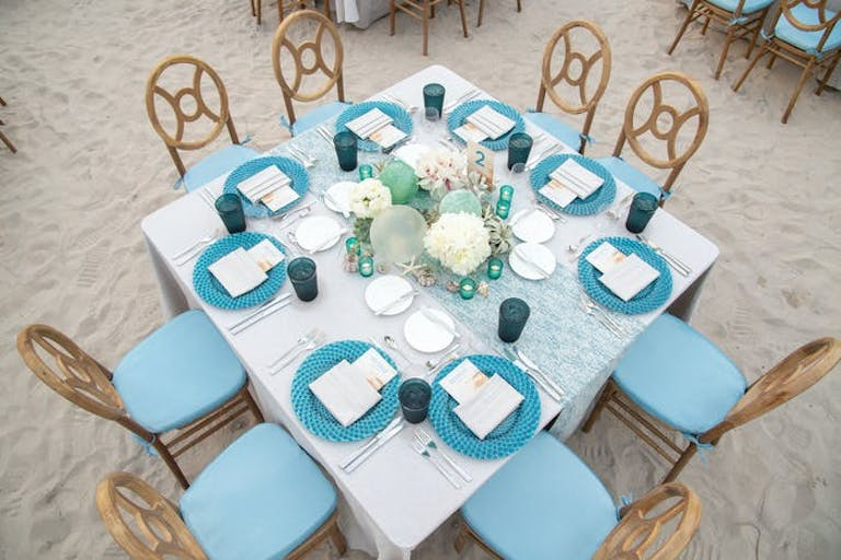 An above view of a square tablescape with a white linen and blue place settings.