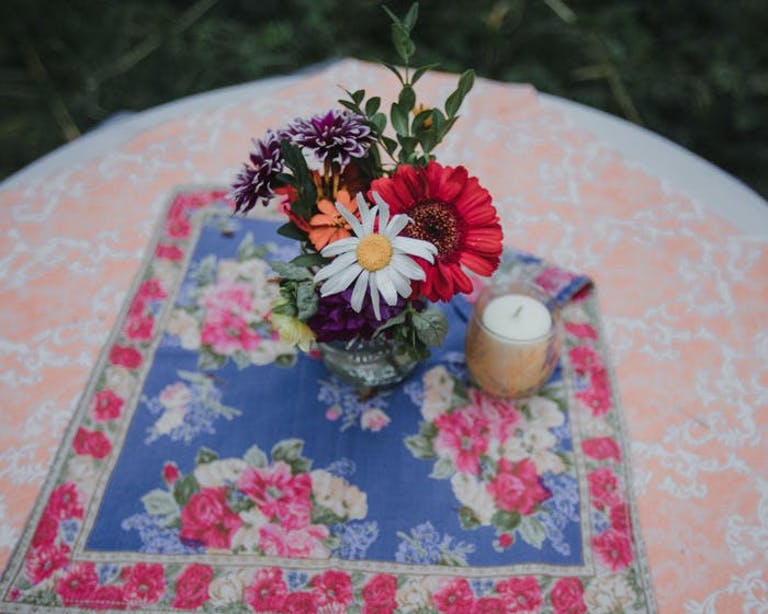 minimal flower arrangement on two patterned table linens