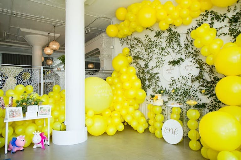 A white room with a balcony covered in sunshine yellow balloons and Ivy on the walls