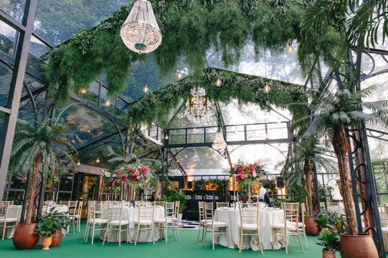the inside of a transparent tent with greenery placed sparsely on the ceiling and chandeliers hang in three different spots. Round tables are placed on the green floor with tall floral centerpieces