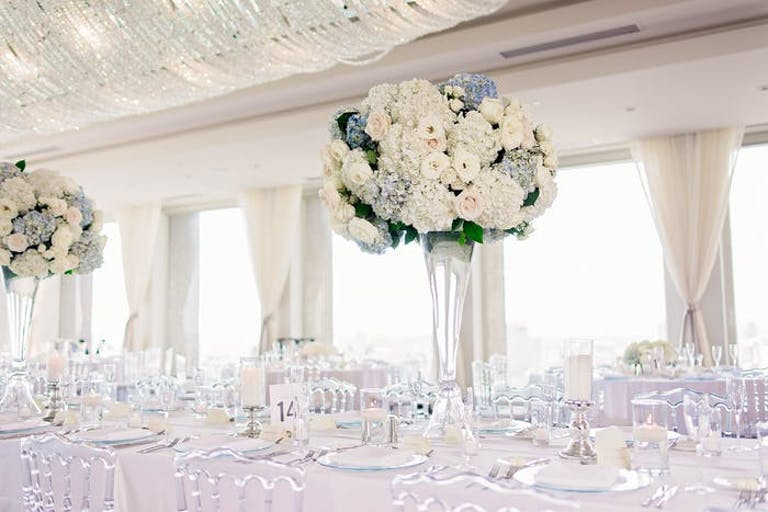 An all white tablescape with a tall floral arrangement and transparent seating
