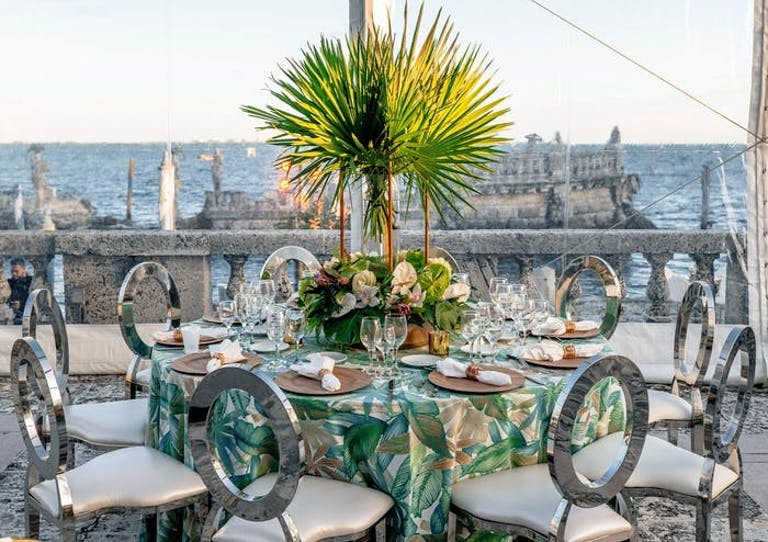 A square table on a rooftop overlooking ruins in the water. Metal chairs surround the table and a green palm leaf is the centerpiece