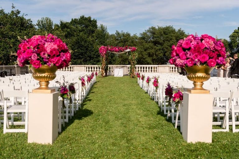 A grassy aisle with white chairs on either side. Pink roses flank the entrance of the aisle.