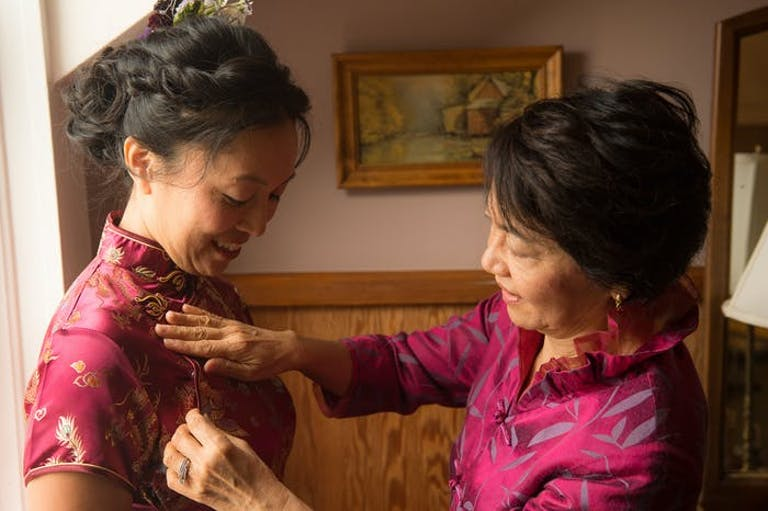 A Mother, wearing a hot pink Cheongsam, smooths out her daughter's hot pink Cheongsam