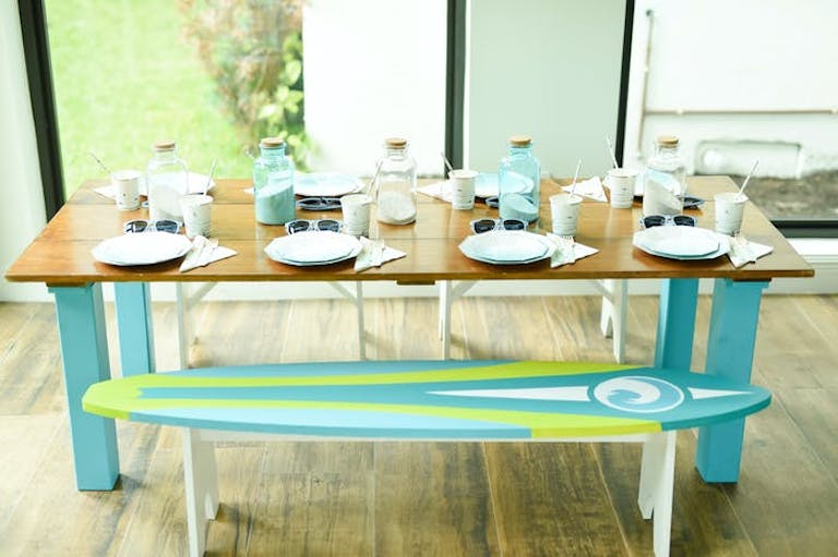 A picnic style table with a wooden finish and place settings. The benches are painted as surf boards