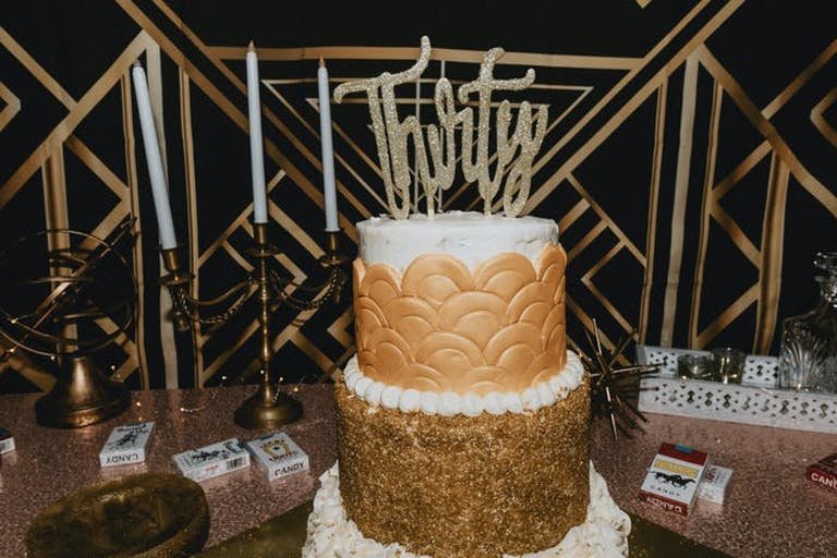 A gold and white cake that has two tiers. Thirty is spelled out in gold sparkling lettering in the top