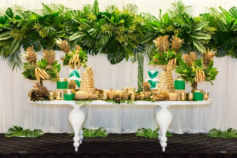 A decor table with greenery hanging above and all accessories painted gold