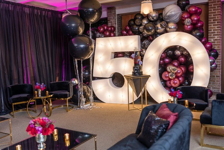 a photo background with a 50 illuminated and pink balloons in the back and sides
