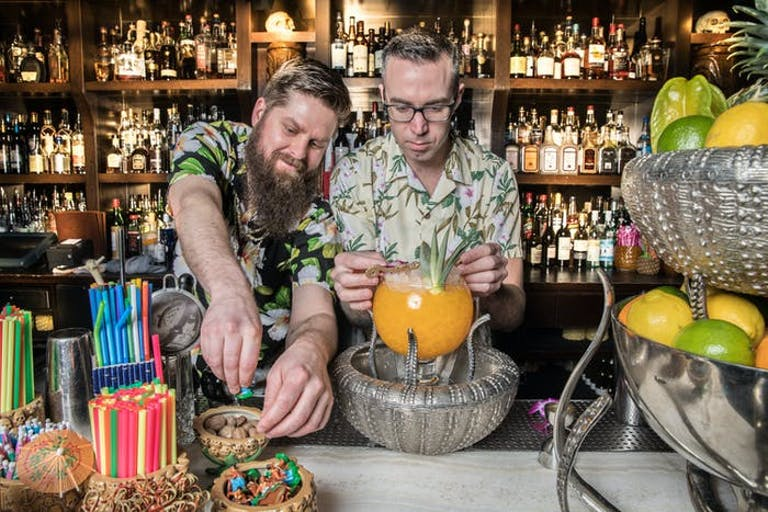 Two men at the bar in tropical shirts making a drink bowl