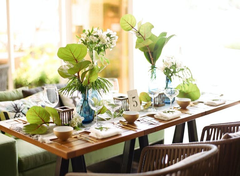 An earth toned photo with a small wooden table with place settings. Green leaves make up the centerpiece