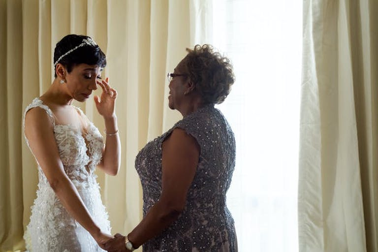 A bride in a white wedding dress wipes away as a tear as her mother holds her hand.