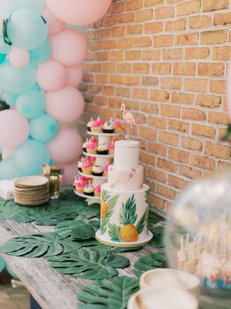 A three tiered cake with pineapples printed on. The table has monstera leaves sitting flat and pink and blue balloons flank the cake