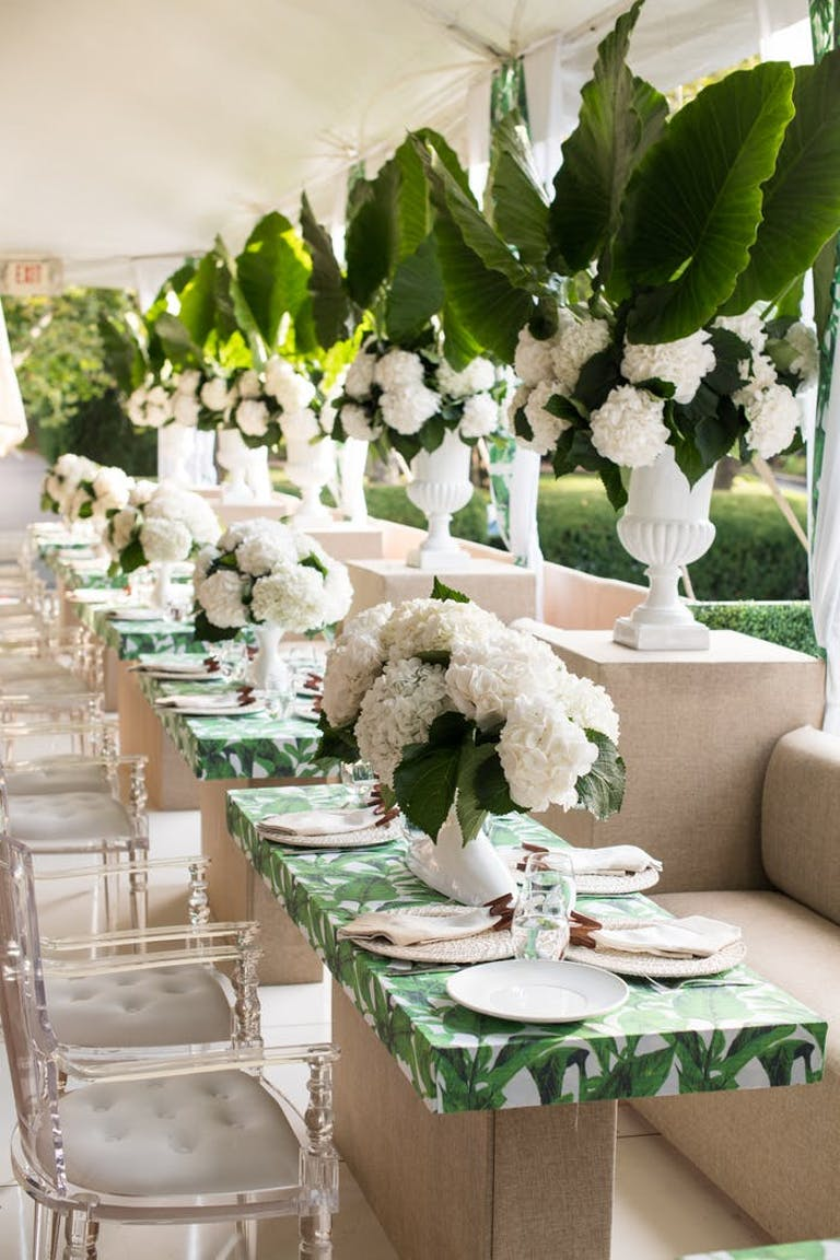 Small individual tables with green and white linens. Translucent chairs surround the tables and tall green and white potted plants are between each table