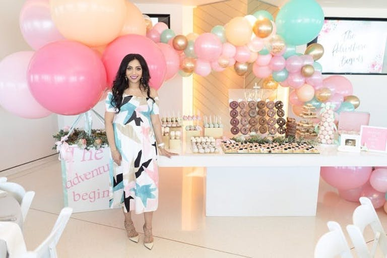 a pregnant woman standing in front of her dessert table with pink, peach and blue balloons