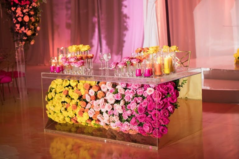 A multicolored floral covered bar with pink lighting