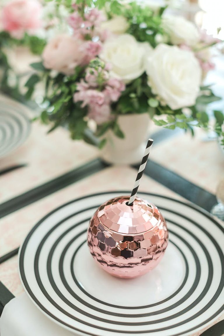 A pink disco ball cup wth a straw sits on a black and white plate. Pink and white florals are in the corner. | PartySlate