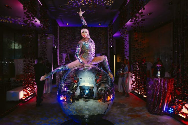 Female Performer Poses on Top of Giant Disco Ball | PartySlate