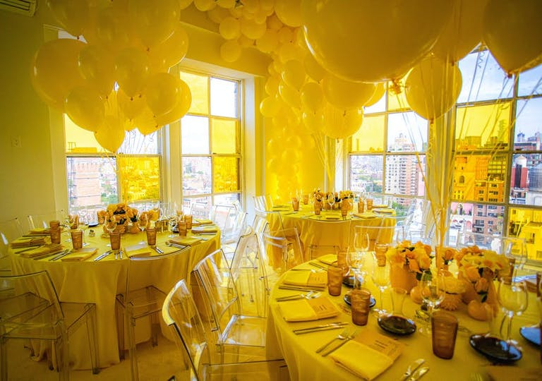 A corner with windows on both sides. Yellow balloons in the center of each table and a glow of yellow throughout the whole room