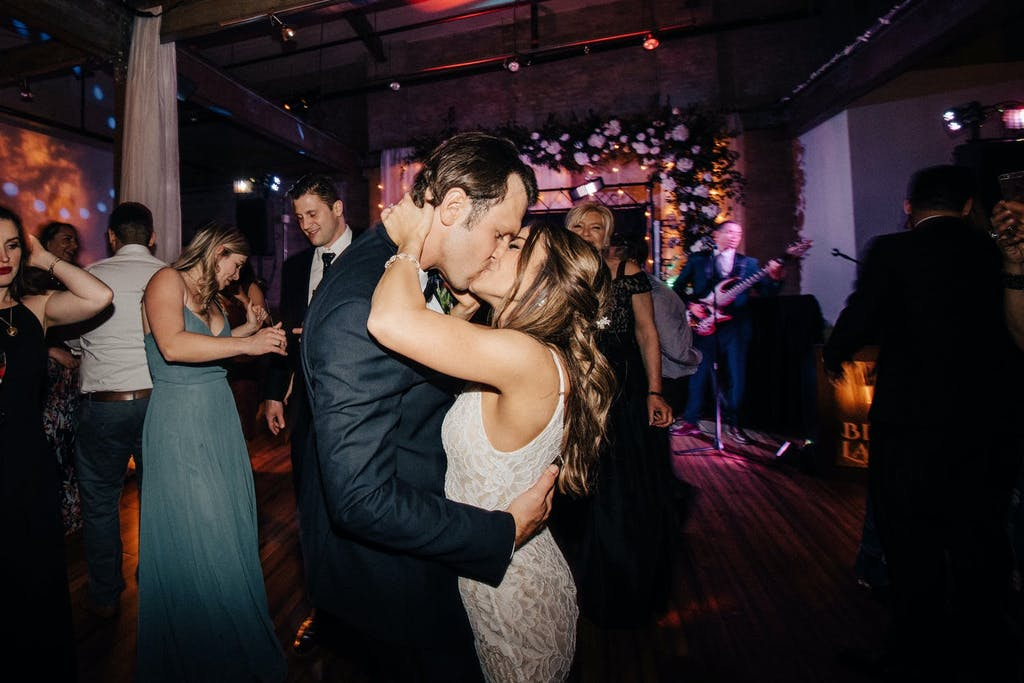 A closeup of a bride and groom kissing with their friends and band performing in the backdrop.