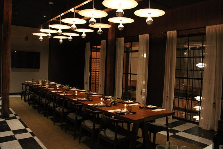 Dimly lit private dining space with banquet table and globed lighting.