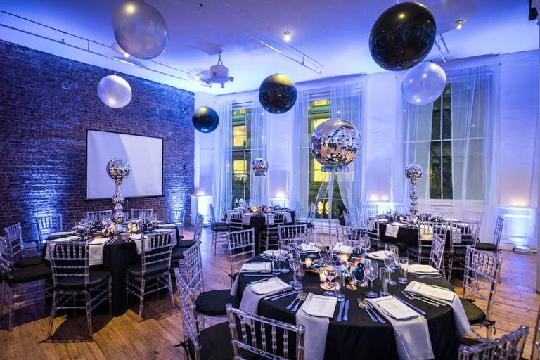An industrial style room lit up blue. Centerpieces are raised disco balls and balloons are on the ceiling