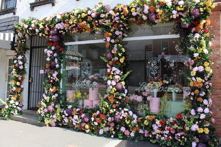 A retail level window with florals surrounding