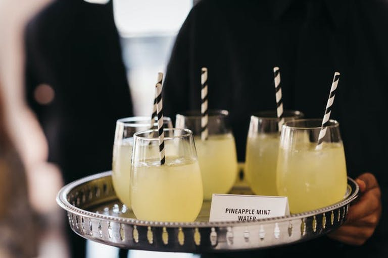 Plate with pineapple juice in glasses and straws