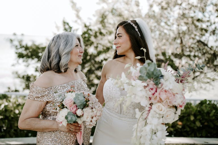 Close up of bride sharing a meaningful look with her mother. Both hold blush and white bouquets with greenery.