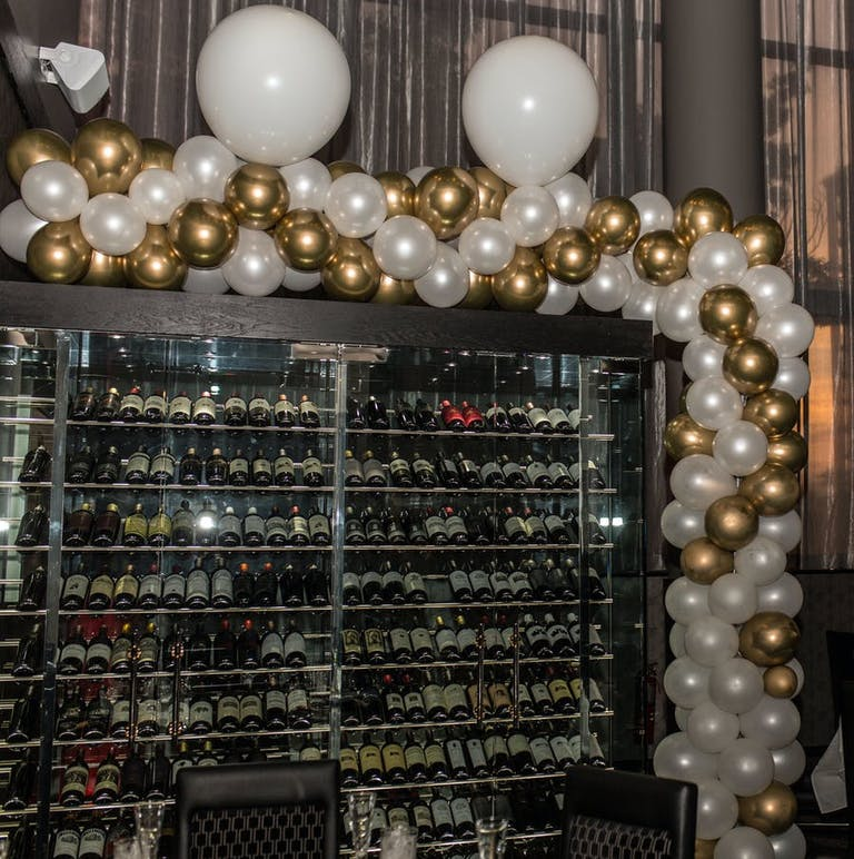 A full wine fridge with white and gold balloons on the border