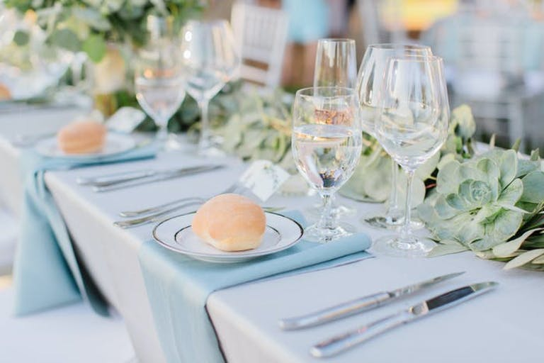 pastel blue table arrangement with a roll on each plate