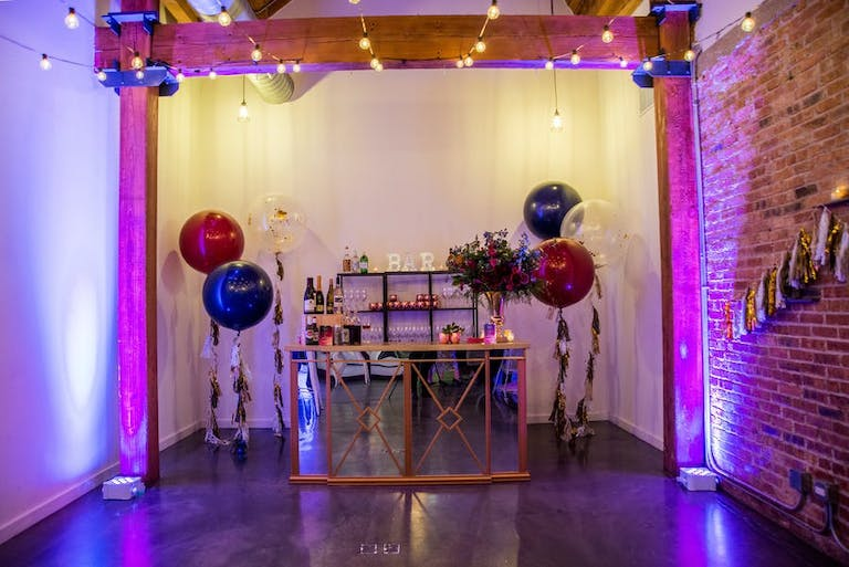 An entrance table with balloons on either side