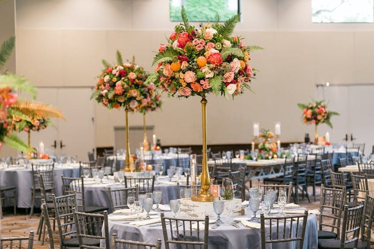 A ballroom with tall centerpieces with coral and pink flowers mixed with greenery