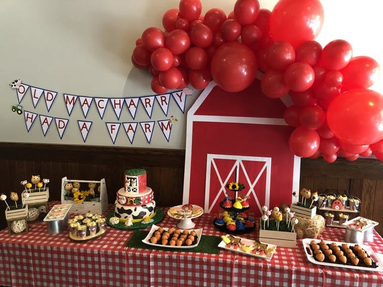 A dessert table with red balloons, a red bar and checkered table linen