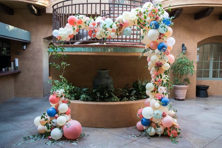 a balcony that jets out onto a walk way covered with balloons