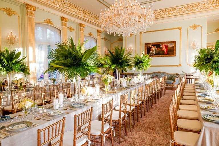 Sunlit ballroom with tall greenery centerpieces