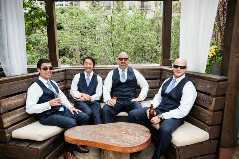 four men wearing white shirts, vests and sunglasses sitting in a semi circle wodden bench.