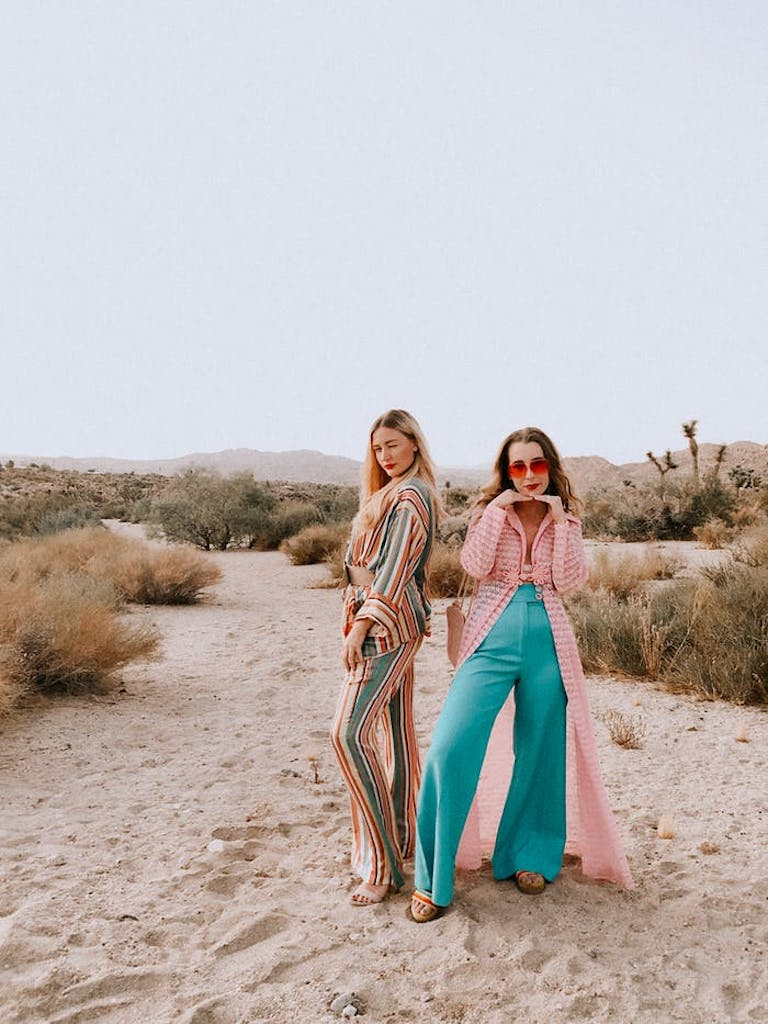 Two young women standing in the sand wearing 70s outfits | PartySlate